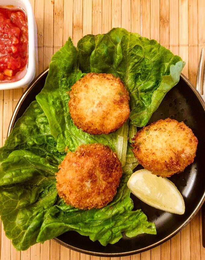 Three arancini on plate next to a dish of tangy homemade tomato sauce.