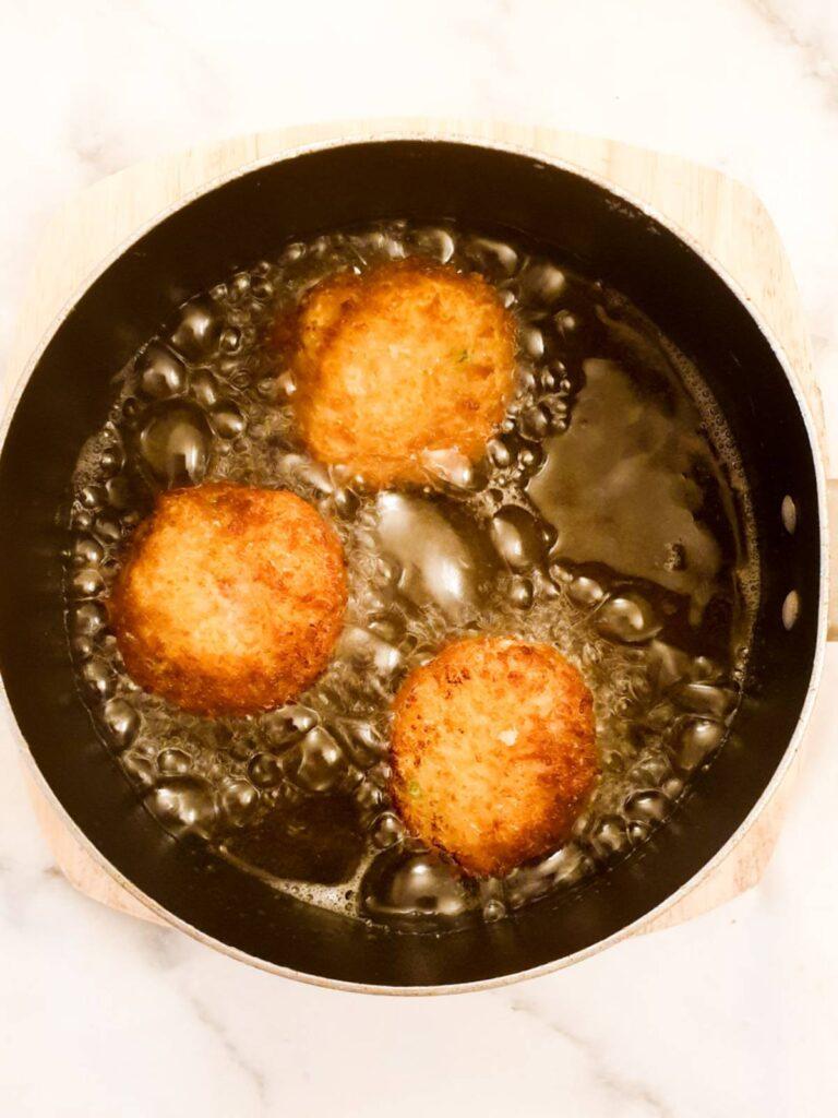 Arancini being deep fried in oil.