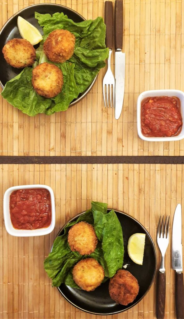 Overhead shot of two plates of arancini balls with bowls of homemade tomato sauce.