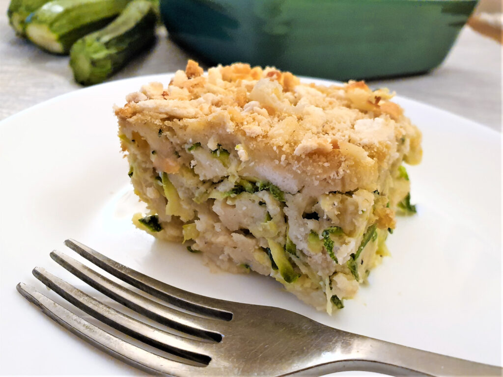 A slice of cheesy zucchini bake on a plate with a fork.