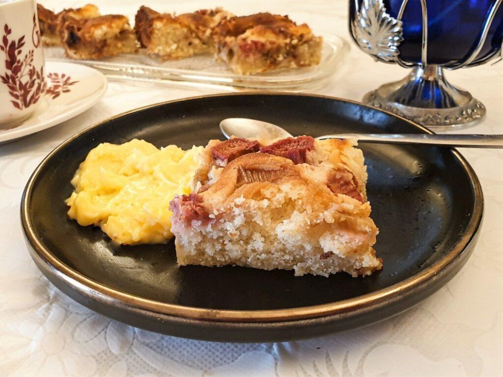 A slice of rhubarb cake on a plate, with custard.