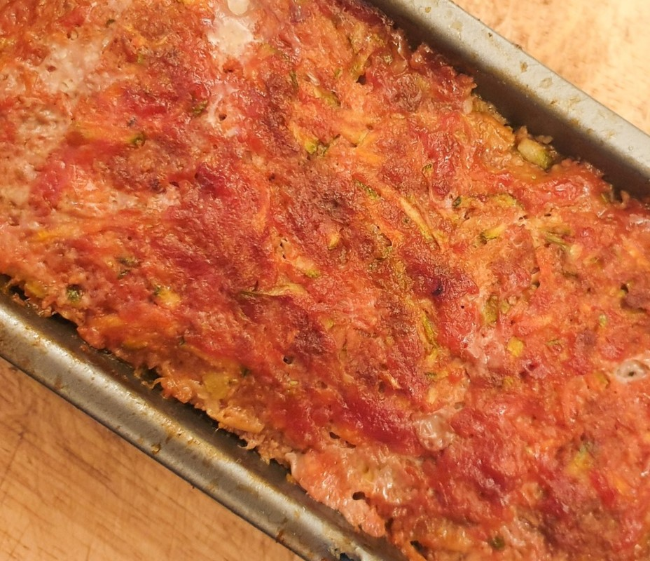 Closeup of a baked meatloaf in a baking tin.