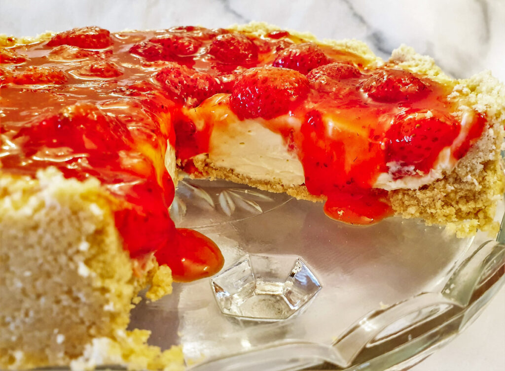 Closeup of no-bake strawberry cheesecake with oozing syrup.
