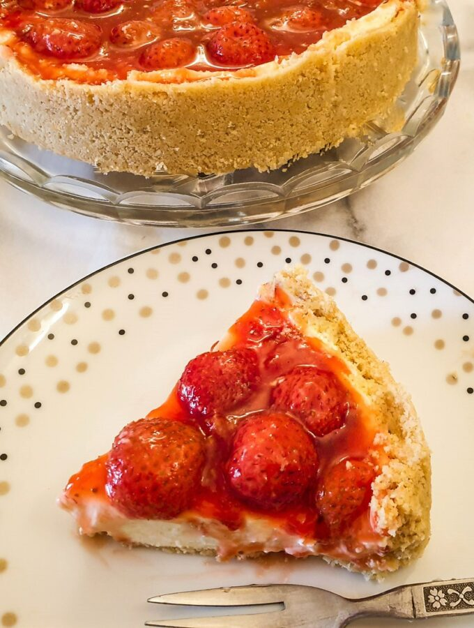 Strawberry cheesecake on a plate next to the whole cheesecake.