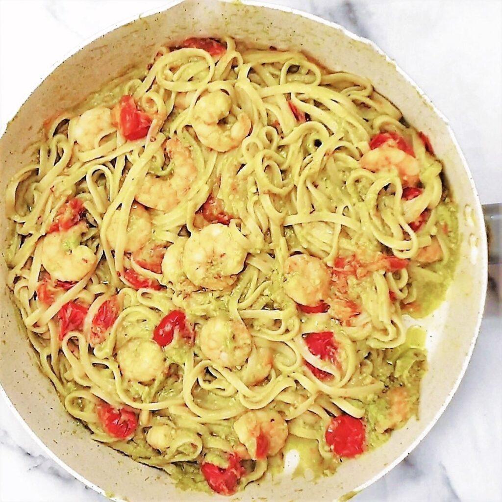 Avocado and shrimp linguine in a pan.