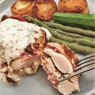 A bacon-wrapped chicken parcel on a plate with vegetables and potatoes.