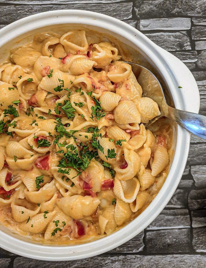 A dish of cheesy barbeque pasta sprinkled with chopped parsley.