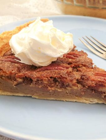 A slice of pecan nut pie, topped with cream, on a plate with a fork.