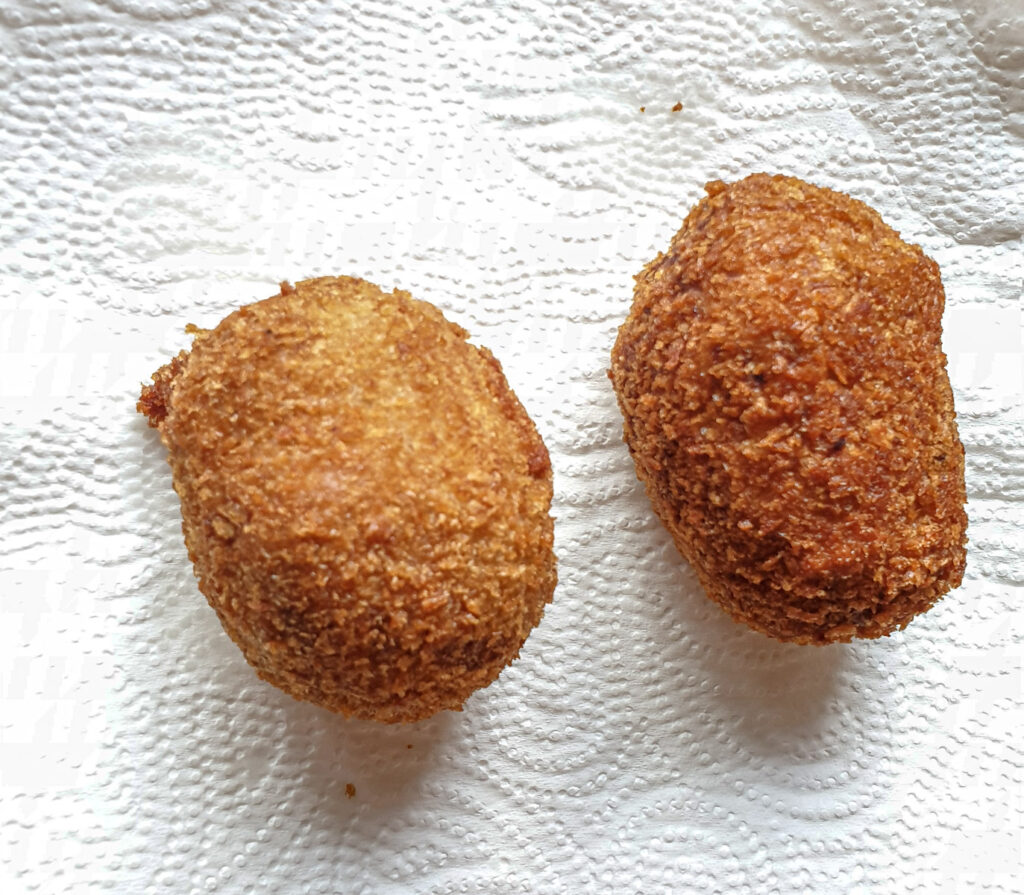 Two deep-fried scotch eggs draining on a paper towel.
