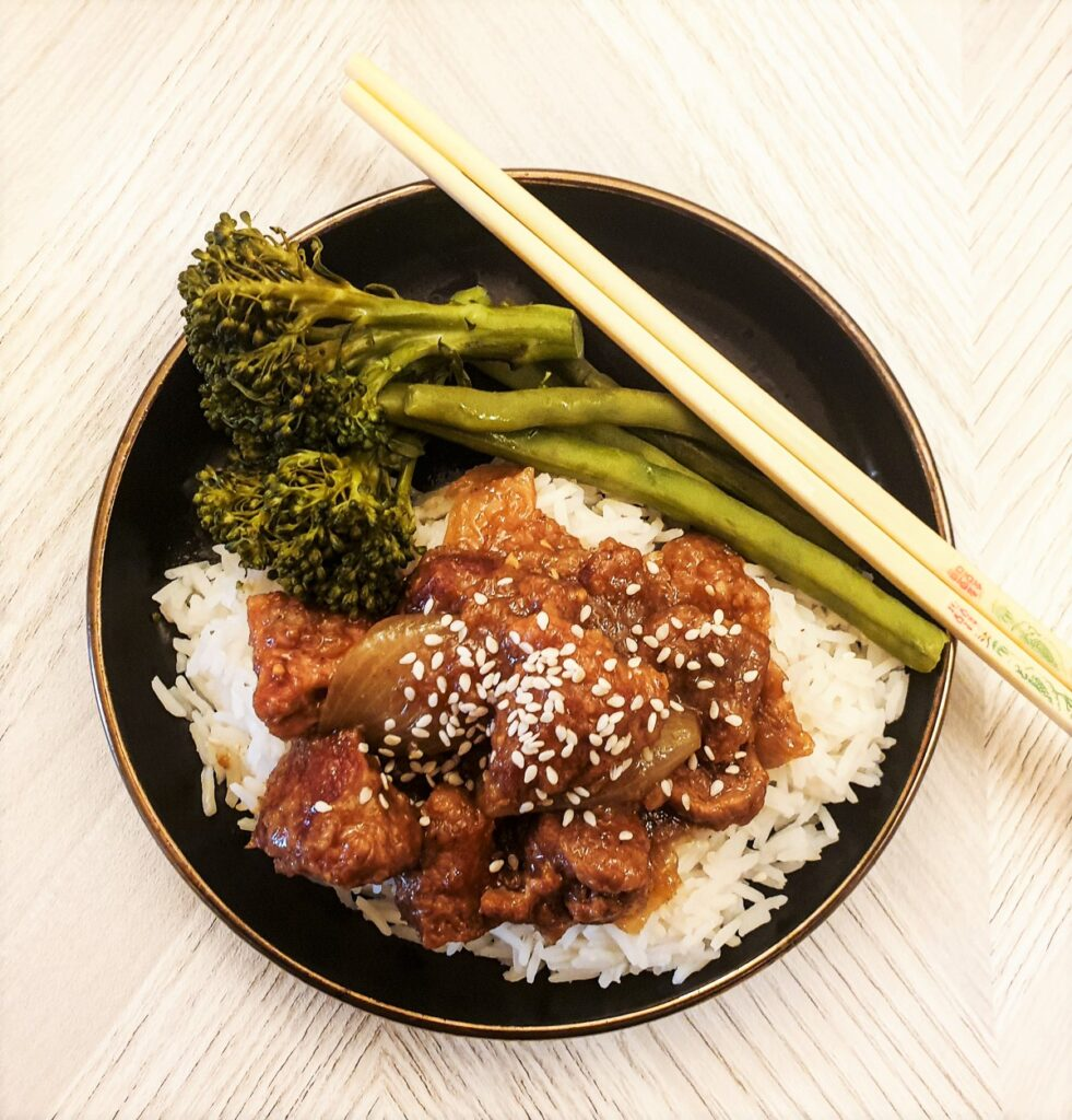 Overhead shot of a plate of sticky Asian pork on a bed of rice, with vegetables.