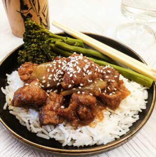 Sticky asian pork on a pile of rice, sprinkled with sesame seeds.