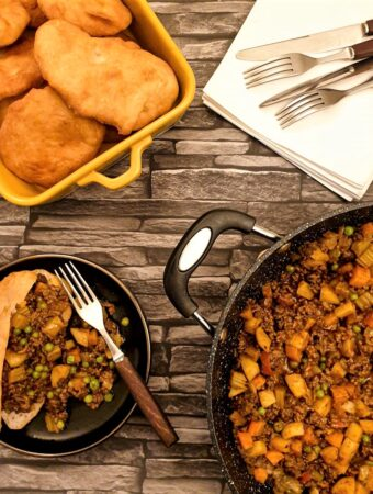 A vetkoek on a plate, filled with curried mince, next to a pan of curried mince and a dish of deep-fried vetkoek.