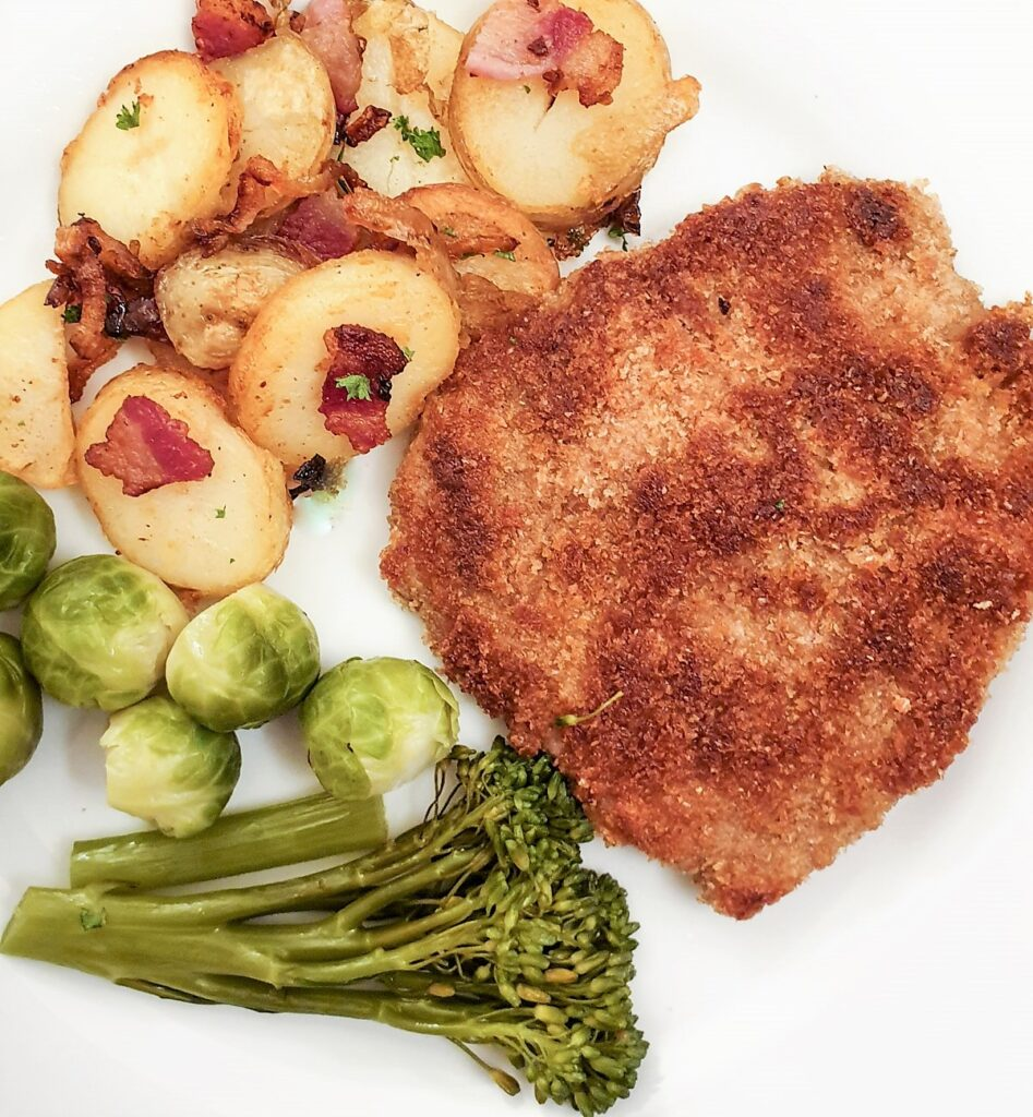 A crispy crumbed beef schnitzel on a plate next to a pile of German fried potatoes.