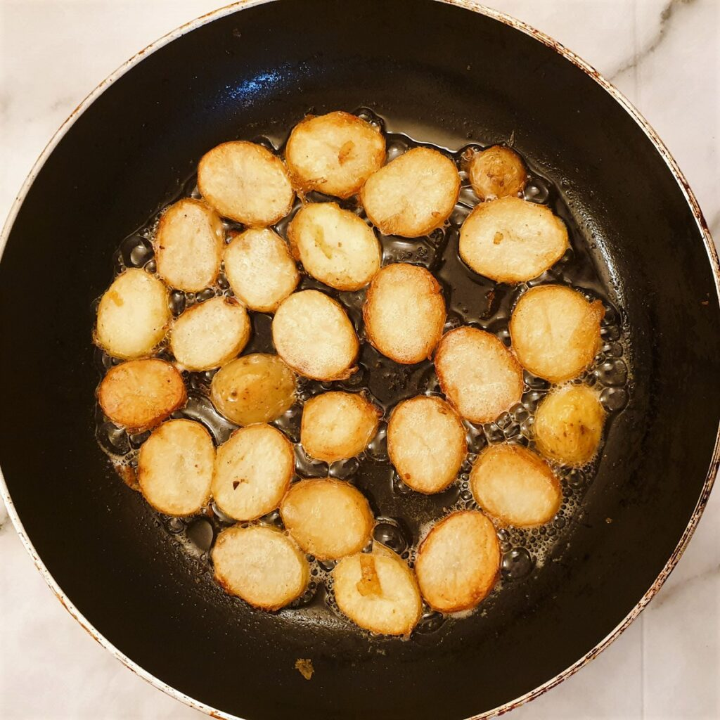 Slices of potatoes frying in a frying pan showing how they brown.