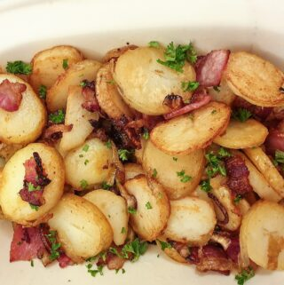 Overhead shot of a dish of German fried potatoes sprinkled with parsley.