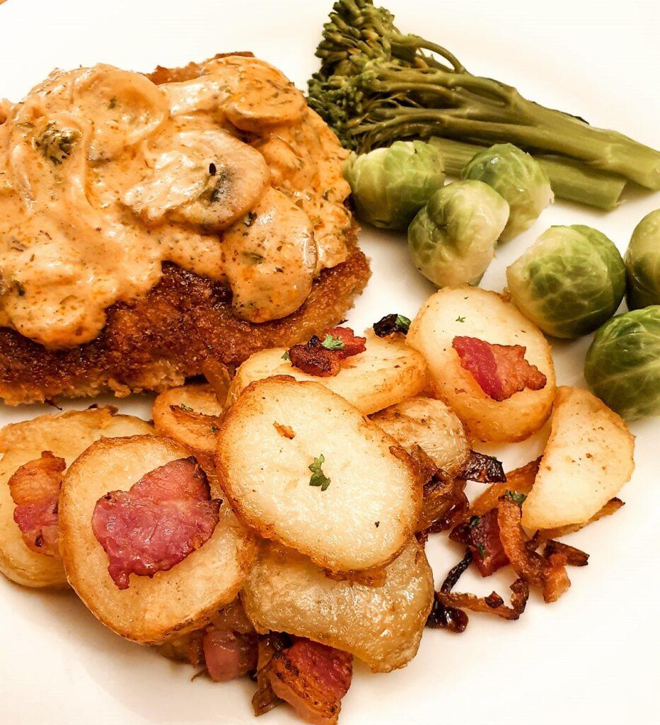 A plate of German fried potatoes served alongside a crispy beef schnitzel and mushroom sauce.