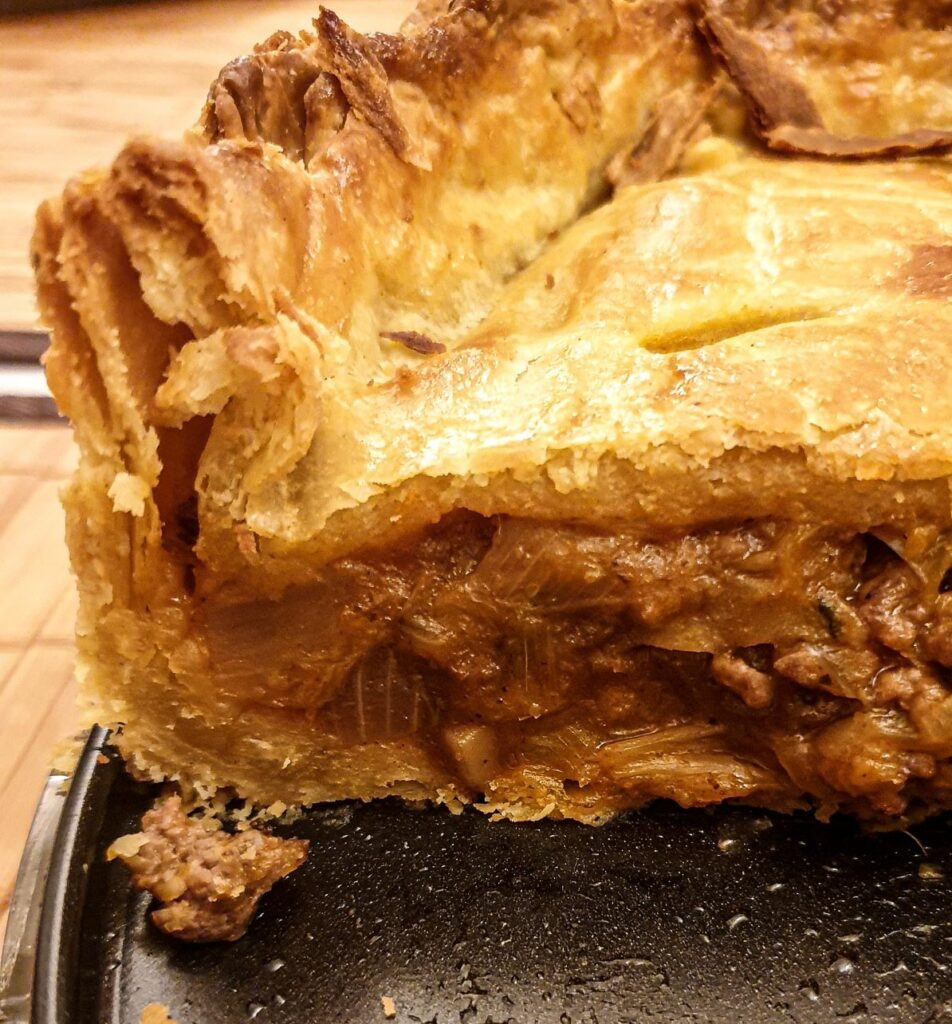 A close up of the inside of the raised beef and onion pie showing the flaky texture of the pastry.