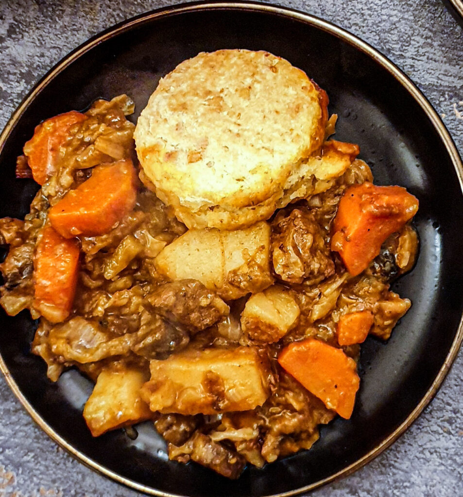 Close up of a plate of beef stew with  cheesy cobbler on the side.