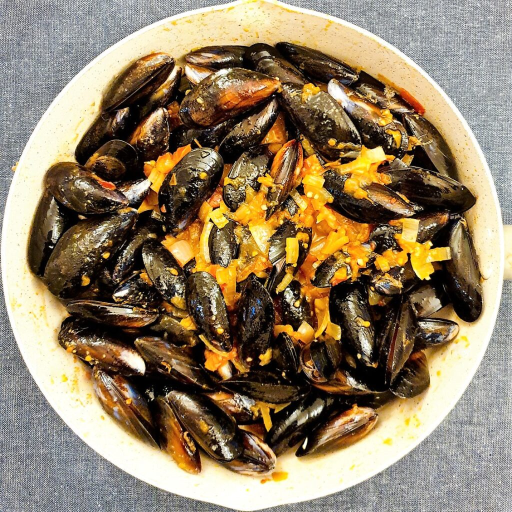 Mussels in a pan mixed with tomato and onion sauce.