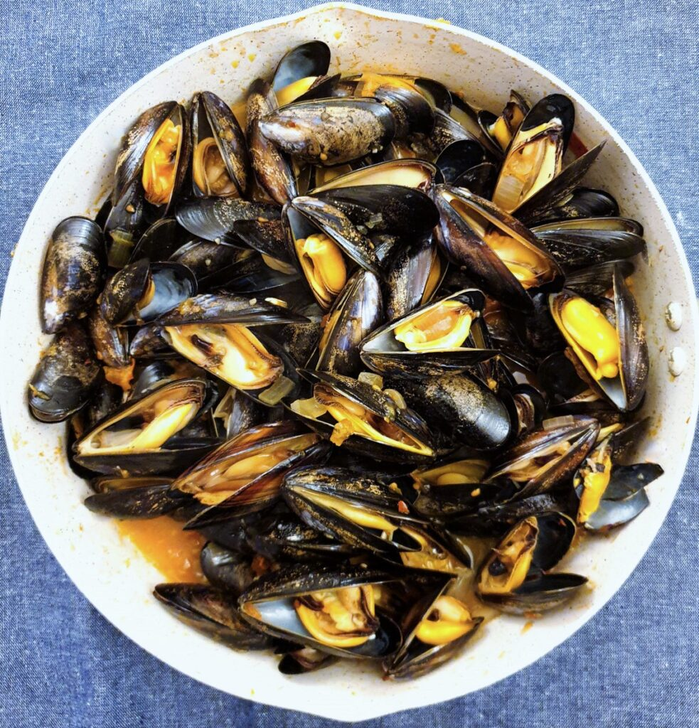 A pan of cooked mussels that have opened.