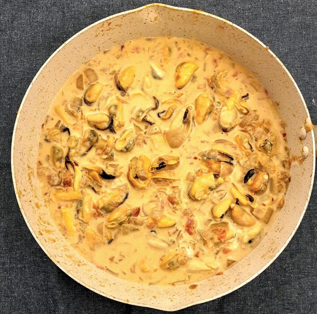 A pan of mussels that have been removed from their shells, in a pan with cream and tomato sauce.