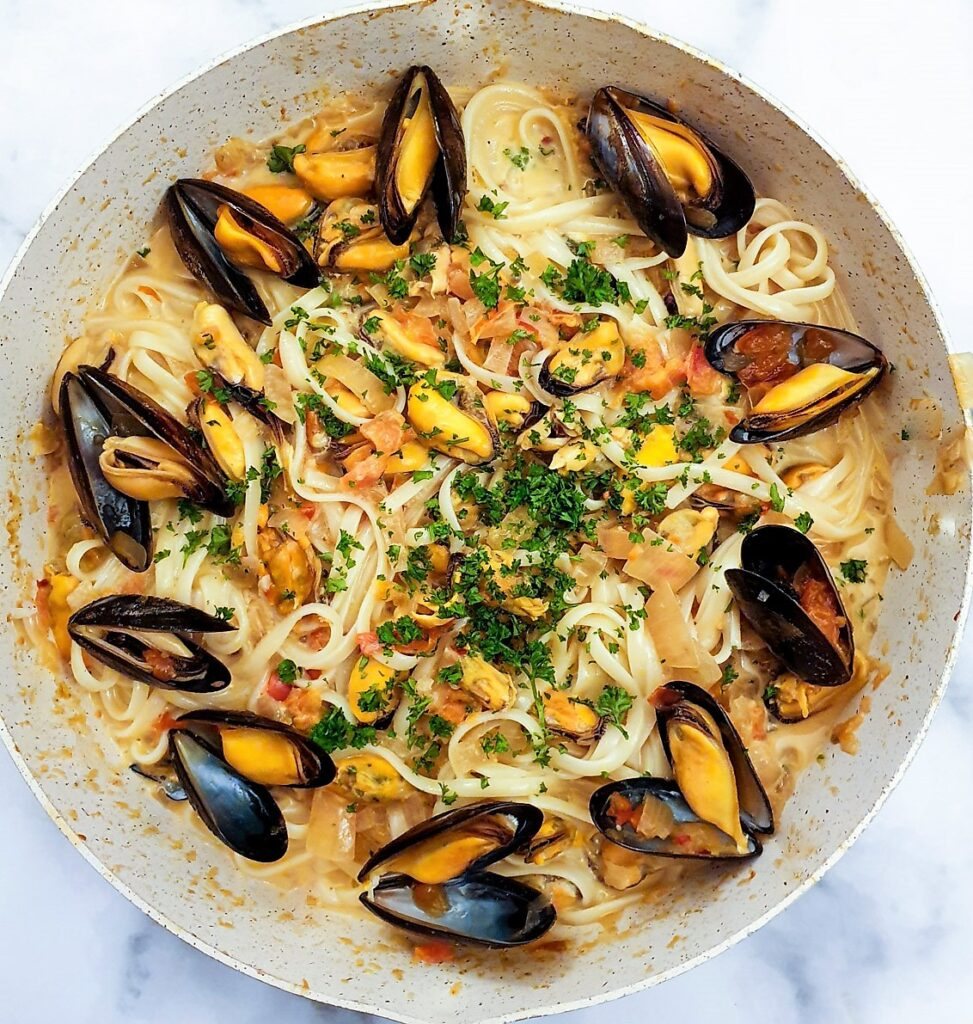 Overhead shot of a pan of mussels in a spicy tomato and onion sauce, served with linguine.