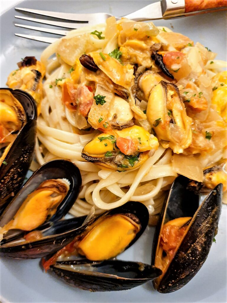Closeup of plate of mussels with pasta in a spicy tomato sauce.