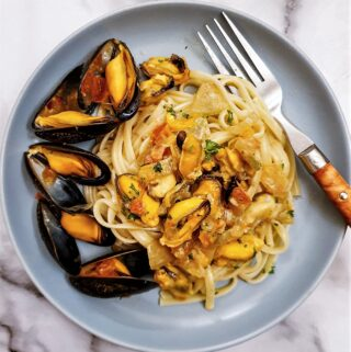 A plate of mussels with pasta, garnished with mussels in their shells.