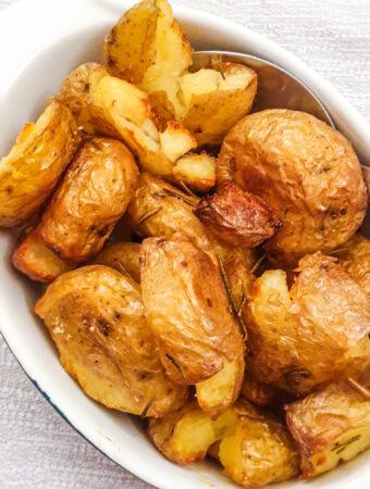 A dish of rosemary smashed potatoes.